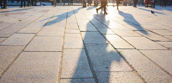 Pedestrian out of focus walking on sidewalk in the city center of a metropolis - rush hour, commuters, walking concept
